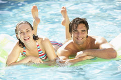 Portrait Of Young Couple Relaxing In Swimming Pool Royalty Free Stock Images