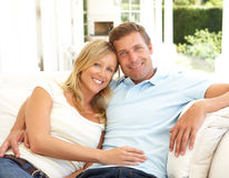 Portrait Of Young Couple Relaxing Together On Sofa Royalty Free Stock Image