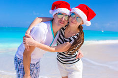 Portrait of young couple in Santa hats enjoy beach Stock Photos