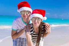 Portrait of young couple in Santa hats enjoy beach Stock Photography