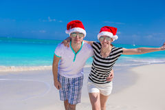 Portrait of young couple in Santa hats enjoy beach Stock Photo