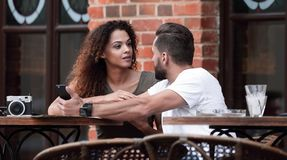 Portrait of a young couple sitting down at a cafe terrace royalty free stock photo