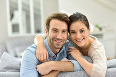 Portrait of young couple sitting at home smiling stock photos