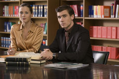 Portrait Of Young Couple Sitting At Library Desk Royalty Free Stock Photos