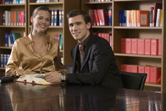 Portrait Of Young Couple Sitting At Library Desk Stock Image