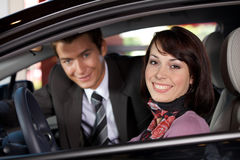 Portrait of young couple sitting in a new car at showroom Stock Photography