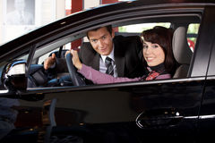 Portrait of young couple sitting in a new car at showroom Stock Photos