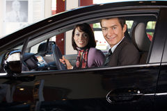 Portrait of young couple sitting in a new car at showroom Royalty Free Stock Image