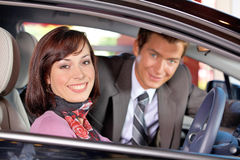 Portrait of young couple sitting in a new car at showroom Stock Image