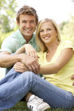 Portrait Of Young Couple Sitting In Park Royalty Free Stock Image
