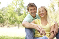 Portrait Of Young Couple Sitting In Park Stock Photo