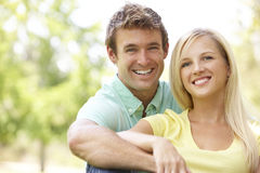 Portrait Of Young Couple Sitting In Park Stock Image