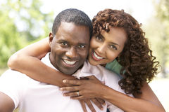 Portrait Of Young Couple Sitting In Park Stock Images