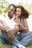 Portrait Of Young Couple Sitting In Park. Smiling To Camera Stock Photography