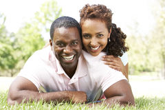 Portrait Of Young Couple Sitting In Park Stock Photos