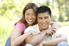 Portrait Of Young Couple Sitting In Park. Portrait Of Young Asian Couple Sitting In Park Smiling Stock Images