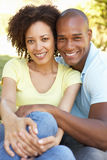 Portrait Of Young Couple Sitting In Park Royalty Free Stock Photos
