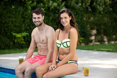 Portrait of young couple sitting at poolside Stock Image