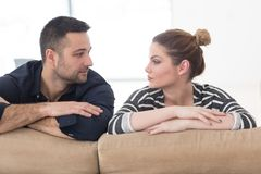 Portrait of young couple sitting on sofa royalty free stock photos