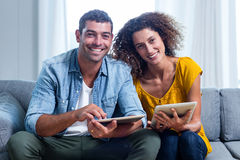 Portrait young couple sitting on sofa and using digital tablet Royalty Free Stock Photos