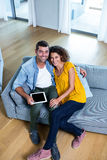 Portrait young couple sitting on sofa and using digital tablet Stock Images