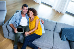 Portrait young couple sitting on sofa and using digital tablet Stock Photography