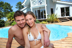 Portrait of young couple sitting by the swimming pool. Portrait of couple sitting by swimming-pool Stock Image