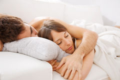 Portrait of a young couple sleeping on bed Stock Photos