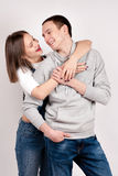 Portrait of a young couple standing against blue gray background Stock Photos