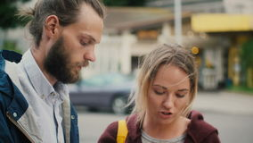 Portrait of young couple standing in the city centre and talking, reading the cards. Man and woman walking outside. Portrait of young beautiful couple standing stock footage