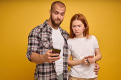 Portrait of a young couple standing with mobile phone, man is using mobile phone while angry girl standing near isolated over royalty free stock photography