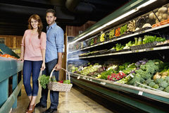 Portrait of young couple standing with vegetable basket in supermarket Royalty Free Stock Images