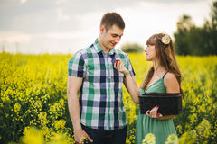 Portrait of young couple standing among yellow flowers in field. Girlfriend with long hair and flower in hair holding black basket Royalty Free Stock Images