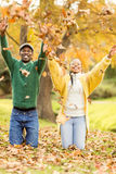 Portrait of a young couple throwing leaves around Royalty Free Stock Image