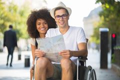 Portrait young couple tourists man in wheelchair. Portrait of young couple of tourists men in wheelchair Stock Image
