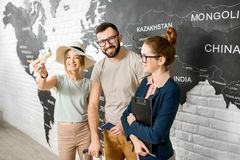 Couple with travel agent at the office. Portrait of a young couple of travelers choosing a summer strip standing with travel agent on the world map background Stock Photo