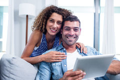 Portrait of young couple using a digital tablet on sofa Stock Images