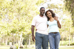 Portrait Of Young Couple Walking In Park. Smiling Stock Photo