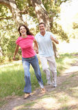 Portrait Of Young Couple Walking In Park Royalty Free Stock Photography