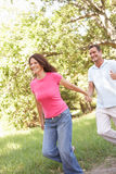 Portrait Of Young Couple Walking In Park. Holding Hands Stock Images