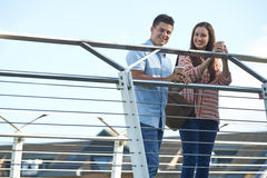 Portrait Of Young Couple Walking To Work Over Bridge royalty free stock photography