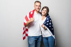Portrait of young couple wrapped in American flag isolated on white background stock photo