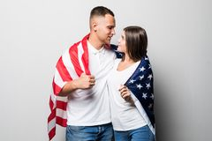 Portrait of young couple wrapped in American flag isolated on white background stock photos