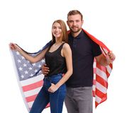 Portrait of young couple wrapped in American flag, isolated on white background. Royalty Free Stock Photos
