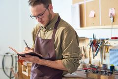 Man Drawing Sketches in Workshop. Portrait of young craftsman drawing sketches holding open book while standing in workshop against table with tools Royalty Free Stock Images