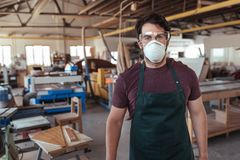 Young craftsman wearing protective gear in his woodworking studio Stock Image