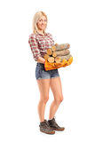 Portrait of a young craftswoman holding fire wood Royalty Free Stock Photography