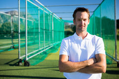 Portrait of young cricketer standing with arms crossed. Against net on field royalty free stock photo