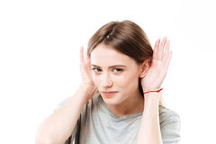 Portrait of a young curious girl trying to hear rumors. Close up portrait of a young curious girl trying to hear rumors keeping hands at her head isolated over Royalty Free Stock Photography