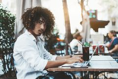 Asian businessman in cafe with laptop and drink. Portrait of a young curly Asian guy in a white shirt using the laptop in an outdoor bar with a glass of a royalty free stock images